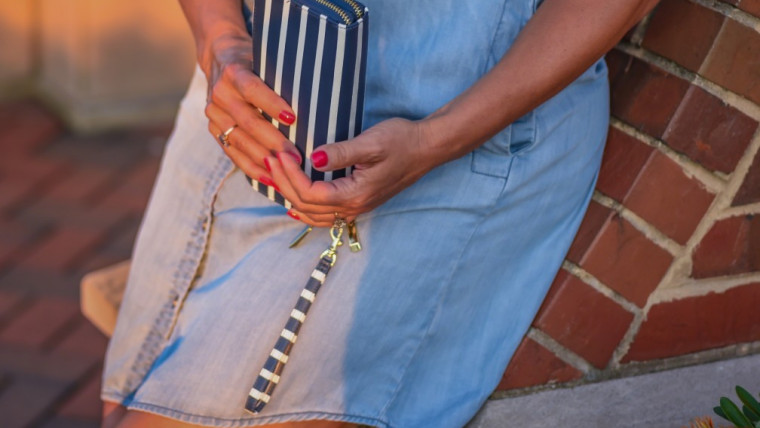 woman-leaning-on-brick-wall-holding-wallet-outside-at-sunset_t20
